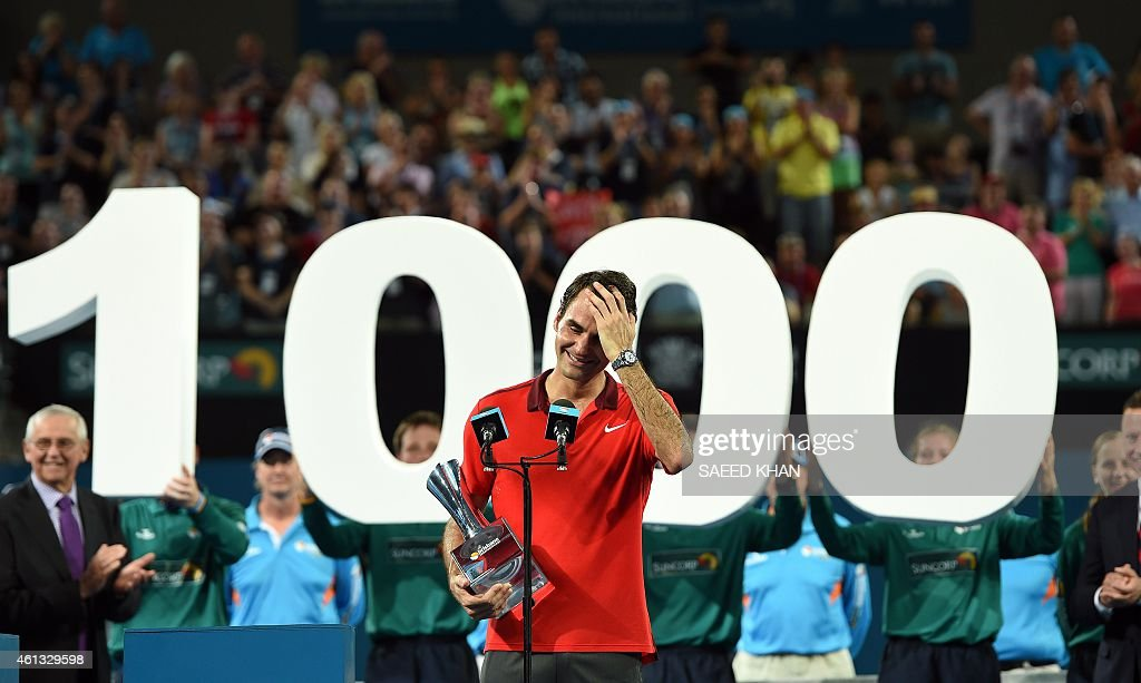 Roger Federer of Switzerland reacts as he celebrates the 1000th victory of his career after beating Milos Raonic of Canada in the men's single final...
