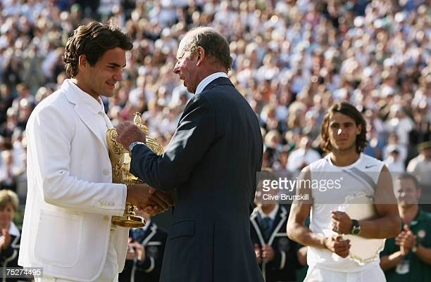 Roger Federer of Switzerland receives the trophy from The Duke of Kent as Rafael Nadal of Spain looks on following the Men's Singles final match...