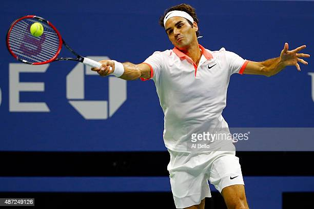 Roger Federer of Switzerland returns a shot against John Isner of the United States during their Men's Singles Fourth Round match on Day Eight of the...