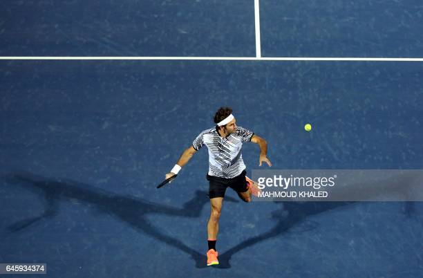 TOPSHOT Roger Federer of Switzerland returns the ball to France's Benoit Paire during their ATP tennis match as part of the Dubai Duty Free...