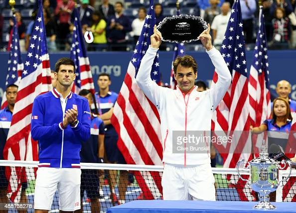 Roger Federer of Switzerland right reacts with his trophy after being defeated Novak Djokovic of Serbia during their Men's Singles Final match on Day...