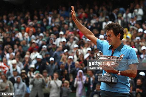 Roger Federer of Switzerland salutes the fans as he holds the trophy following victory during the Men's Singles Final match against Robin Soderling...