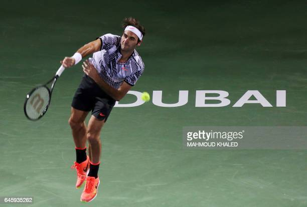 Roger Federer of Switzerland serves the ball to France's Benoit Paire during their ATP tennis match as part of the Dubai Duty Free Championships on...