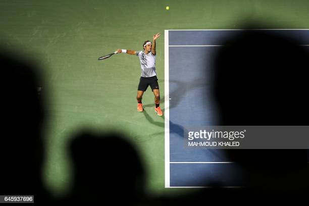 TOPSHOT Roger Federer of Switzerland serves the ball to France's Benoit Paire during their ATP tennis match as part of the Dubai Duty Free...
