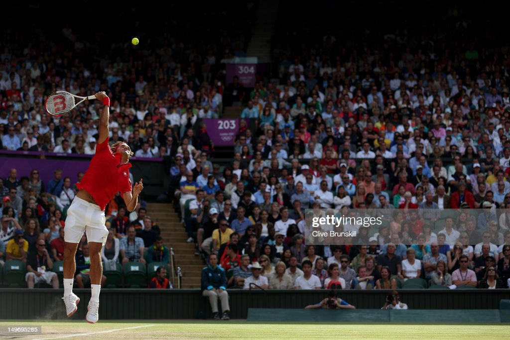 <a gi-track='captionPersonalityLinkClicked' href=/galleries/search?phrase=Roger+Federer&family=editorial&specificpeople=157480 ng-click='$event.stopPropagation()'>Roger Federer</a> of Switzerland serves the ball to John Isner of the United States during the Quarterfinal of Men's Singles Tennis on Day 6 of the London 2012 Olympic Games at Wimbledon on August 2, 2012 in London, England.