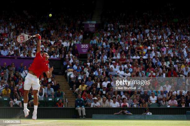 Roger Federer of Switzerland serves the ball to John Isner of the United States during the Quarterfinal of Men's Singles Tennis on Day 6 of the...