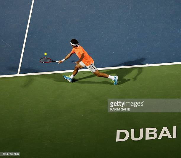 Roger Federer of Switzerland serves the ball to World number one Novak Djokovic of Serbia during their final match on the fifth day of the ATP Dubai...