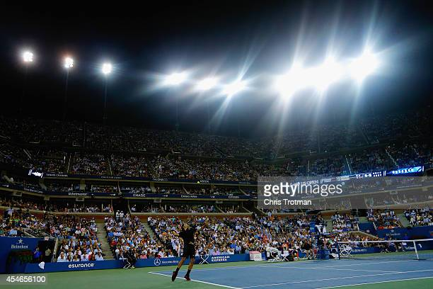 Roger Federer of Switzerland serves to Gael Monfils of France during their men's singles quarterfinal match on Day Eleven on Day Eleven of the 2014...