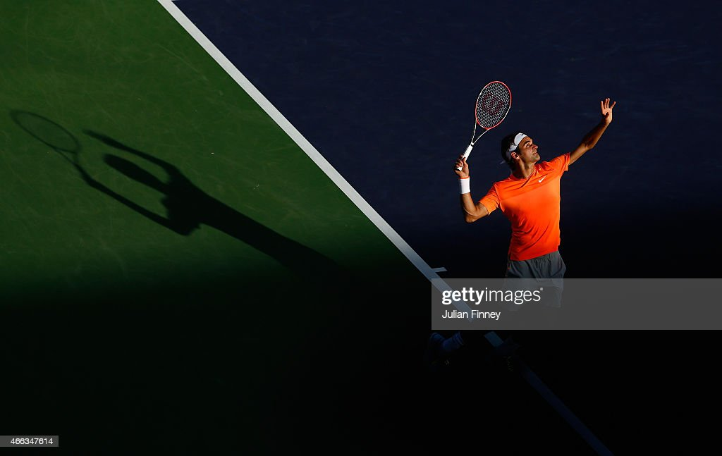 Roger Federer of Switzerland serves with Michael Lammer of Switzerland in their doubles match against Nenad Zimonjic and Marcin Matkowski of Poland...