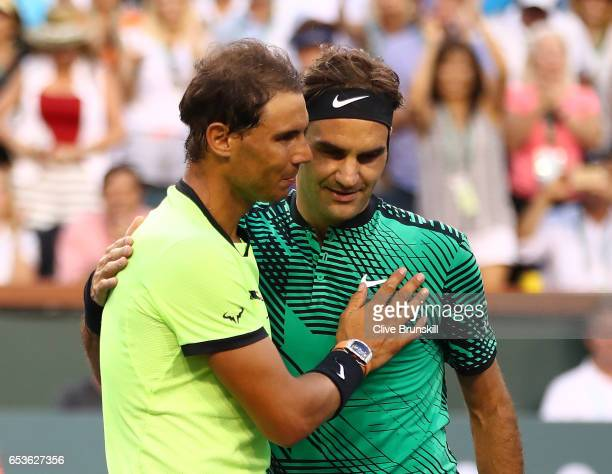 Roger Federer of Switzerland shakes hands at the net after his straight sets victory against Rafael Nadal of Spain in their fourth round match during...