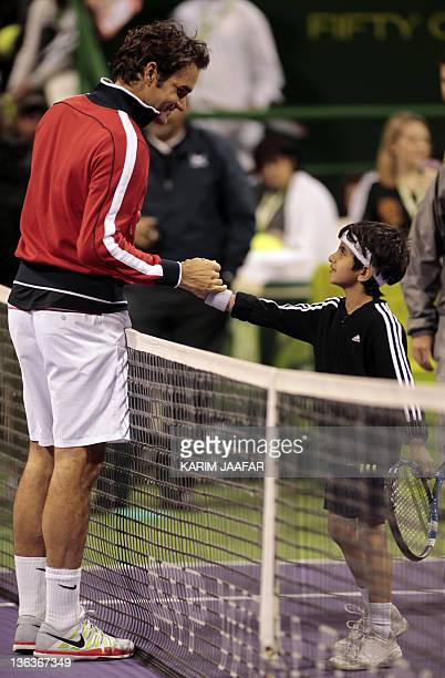 Roger Federer of Switzerland shakes hands with a Qatari boy after winning his ATP Qatar Open tennis match against Nikolay Davydenko of Russia at the...