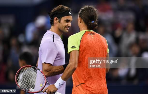 Roger Federer of Switzerland shakes hands with Alexandr Dolgopolov of Ukraine the Men's singles match against on day 5 of 2017 ATP Shanghai Rolex...