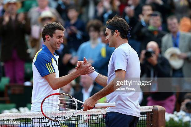 Roger Federer of Switzerland shakes hands with Gilles Simon of France after their Men's Singles match during day eight of the French Open at Roland...