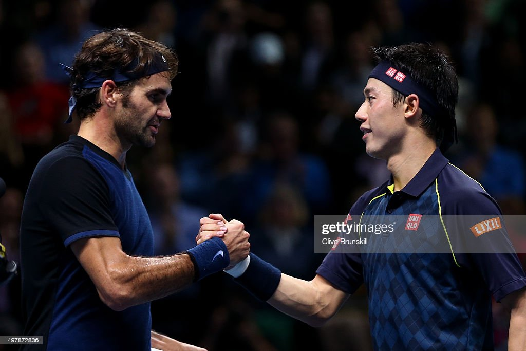 Roger Federer of Switzerland (L) shakes hands with Kei Nishikori of Japan (R) after his victory in their men's singles match on day five of the Barclays ATP World Tour Finals at the O2 Arena on November 19, 2015 in London, England.