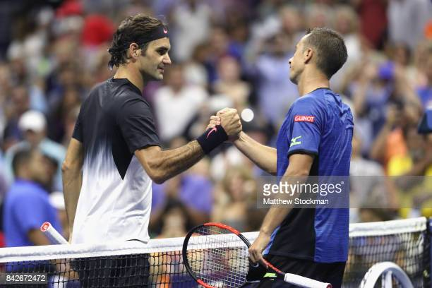 Roger Federer of Switzerland shakes hands with Philipp Kohlschreiber of Germany after defeating him in their men's singles fourth round match on Day...