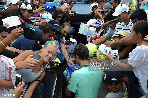 Roger Federer of Switzerland signes autographs for fans after winning a final match against David Ferrer of Spain on day 9 of the Western Southern...