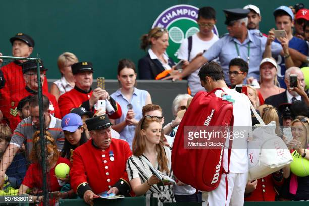 Roger Federer of Switzerland signs autographs for fans after the Gentlemen's Singles first round match against Alexandr Dolgopolov of Ukraine on day...