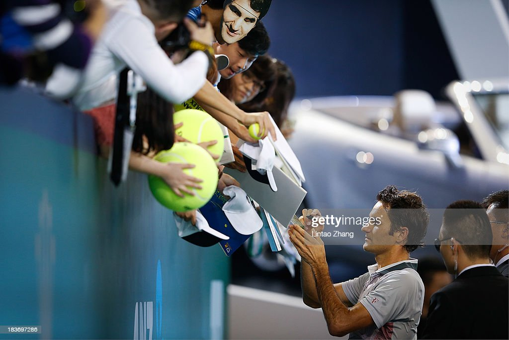 Roger Federer of Switzerland signs for fans after his win against Andreas Seppi of Italy during day three of the Shanghai Rolex Masters at the Qi Zhong Tennis Center on October 9, 2013 in Shanghai, China.