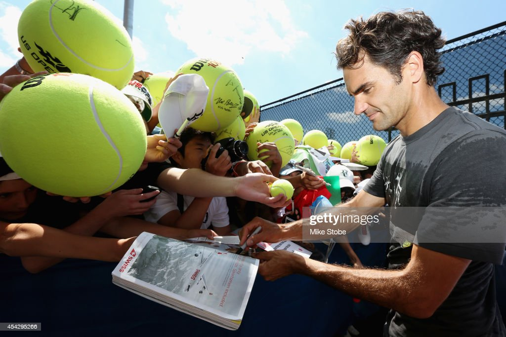 Roger Federer of Switzerland signs his autograph for fans on Day Four of the 2014 US Open at the USTA Billie Jean King National Tennis Center on...