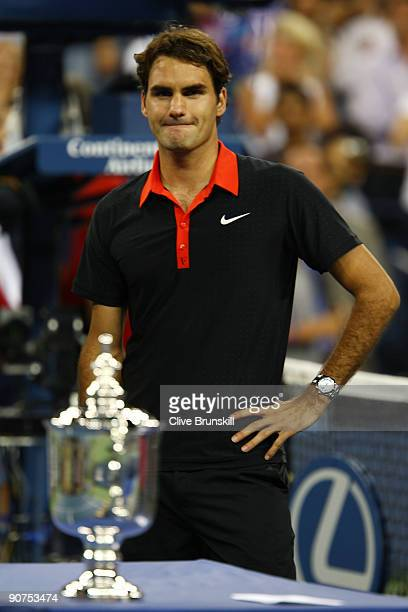 Roger Federer of Switzerland stands by the trophy after the Men's Singles final against Juan Martin Del Potro of Argentina on day fifteen of the 2009...