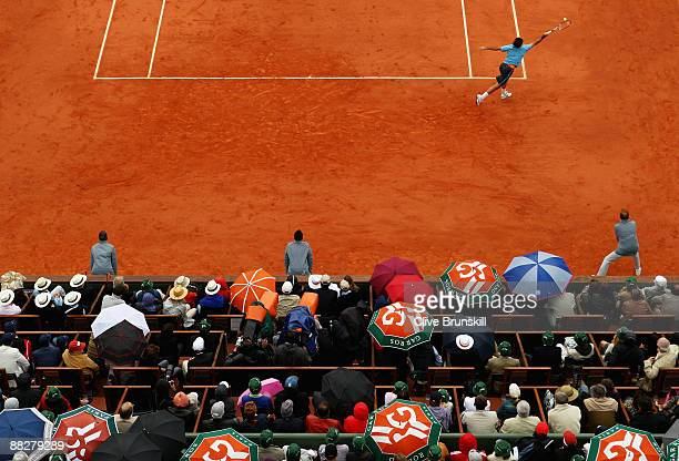 Roger Federer of Switzerland stretches to hit a forehand as the crowd shelters from a heavy rain shower during the Men's Singles Final match against...