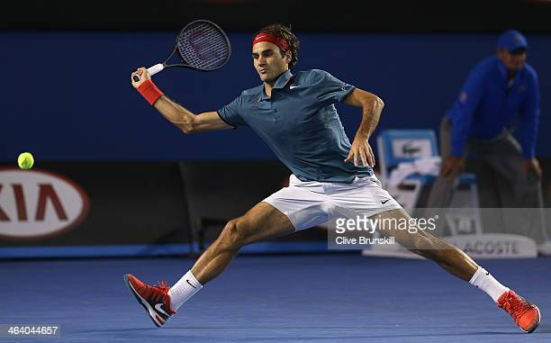 Roger Federer of Switzerland stretches to play a forehand in his fourth round match against JoWilfried Tsonga of France during day eight of the 2014...