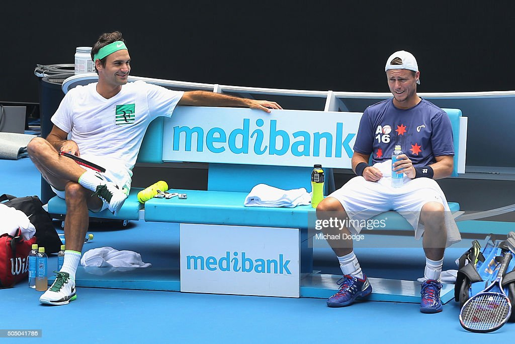 Roger Federer of Switzerland talks with Lleyton Hewitt of Australia during a practice session ahead of the 2016 Australian Open at Melbourne Park on...