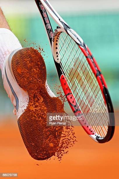 Roger Federer of Switzerland taps the clay off his shoe with his racquet during his Men's Singles Second Round match against Jose Acasuso of...