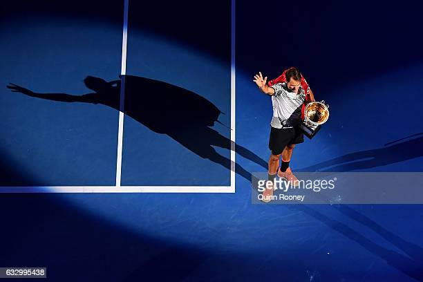Roger Federer of Switzerland thanks the crowd while holding the Norman Brookes Challenge Cup after winning the Men's Final match against Rafael Nadal...