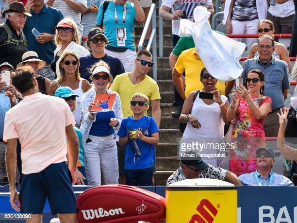Roger Federer of Switzerland throws his towel towards the fans after defeating Roberto Bautista Agut of Spain 64 64 during day eight of the Rogers...