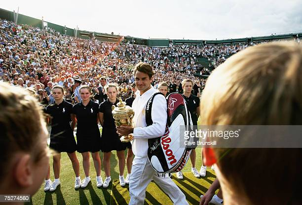 Roger Federer of Switzerland walks off court with the trophy as he celebrates victory following the Men's Singles final match against Rafael Nadal of...