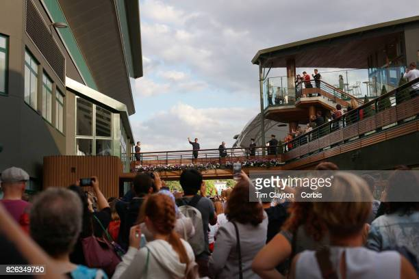 Roger Federer of Switzerland waves to fans after his victory in the Mens' Singles Quarter Final during the Wimbledon Lawn Tennis Championships at the...