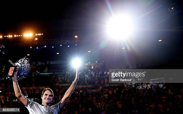 Roger Federer of Switzerland waves to fans in the crowd as he does a lap of honour with the Norman Brookes Challenge Cup after winning the Men's...
