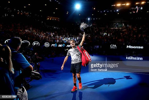 Roger Federer of Switzerland waves to fans in the crowd as he does a victory lap of the court with the Norman Brookes Challenge Cup after winning the...
