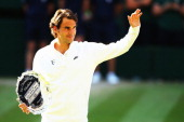 Roger Federer of Switzerland waves to the fans as he holds the runner up trophy after the Gentlemen's Singles Final match against Novak Djokovic of...
