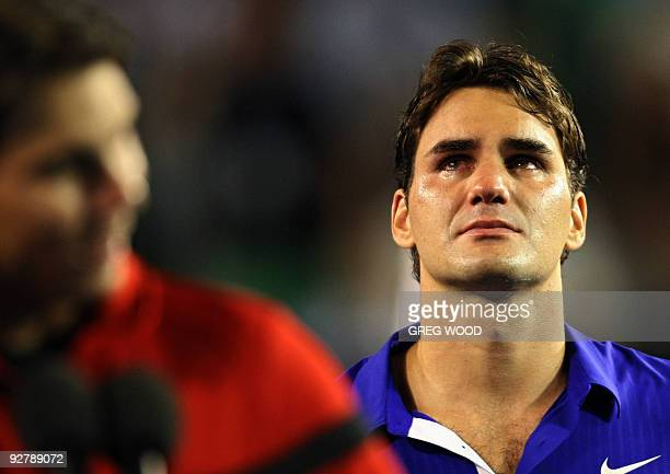 Roger Federer of Switzerland weeps as champion Rafael Nadal of Spain talks at the trophy presentation in the men's tennis final on day 14 of the...