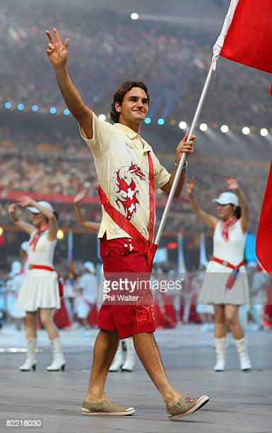 Roger Federer of the Switzerland Olympic men's tennis team carries his country's flag to lead out the delegation during the Opening Ceremony for the...