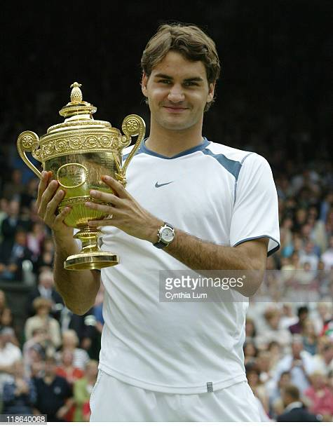 Roger Federer raises the championship trophy after defeating Andy Roddick in the Gentlemen's singles final at Wimbledon London July 3 2005 Federer...