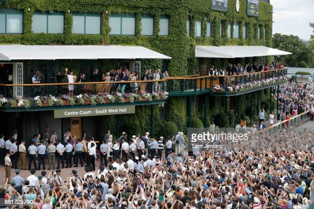 Roger Federer shows the trophy to the huge crowd at the front of the clubhouse after winning the men's singles final against Marin Cilic on Centre...