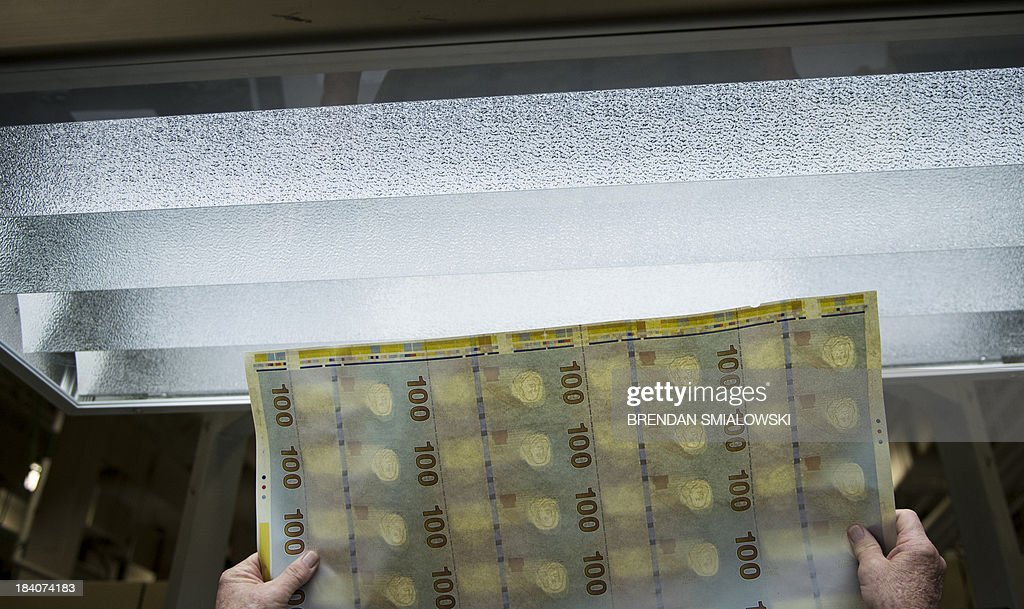 Roger Finley inspects the back of a sheet of the new 100 USD bills at the US Bureau of Engraving and Printing's Western Currency Facility on October 11, 2013 in Fort Worth, Texas. The facility is currently the sole producer of the new 100 USD bill. The bill went into circulation on October 8 and includes new security features such as a purple band with moving images, ink that changes color with the angle as well as a new more colorful design.