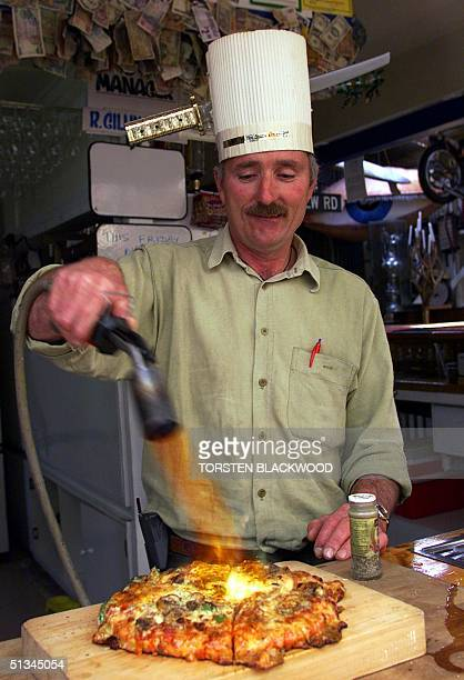 Roger Gillingham uses a flame thrower to cook pizza 01 December 1999 at his eccentric watering hole known as The Smash Palace in Gisborne the first...