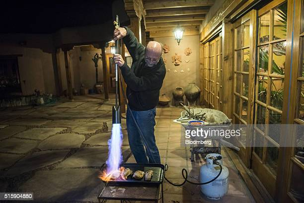 Roger Hunter chief technology officer for QTS Capital Management LLC uses a propane torch to finish cooking chicken breasts in his home in Las Cruces...