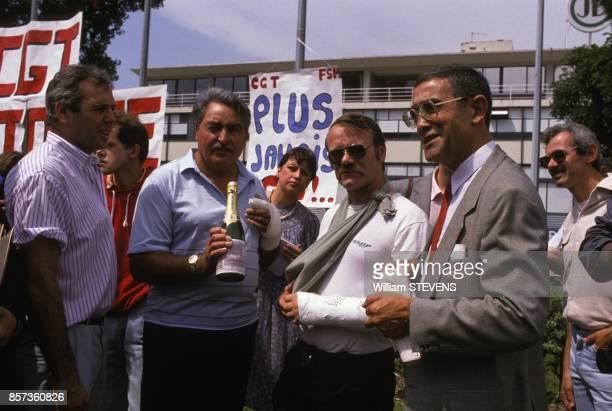 Roger Lancry a droite secretaire general CGT Livre avec des employes lors de la reprise du travail a l'imprimerie Didier le 1er aout 1988 a Paris...