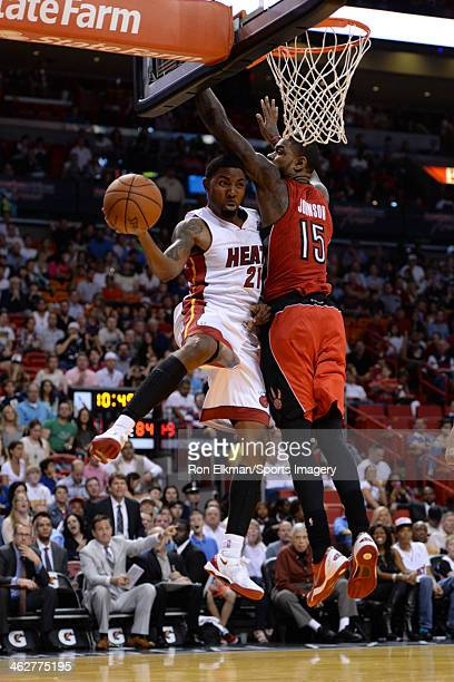 Roger Mason Jr #21 of the Miami Heat shoots and is guarded by Amir Johnson of the Toronto Raptors at AmericanAirlines Arena on January 5 2014 in...