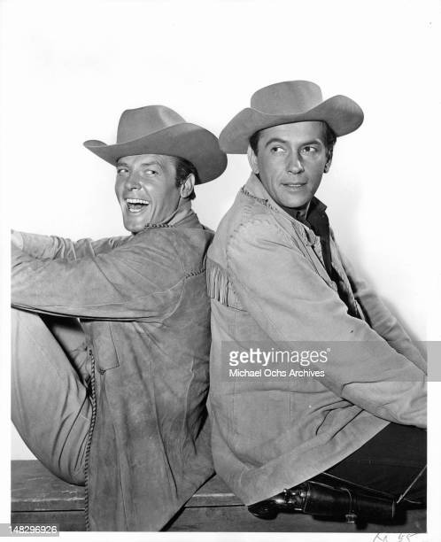 Roger Moore and Jack Kelly in western attire sitting back to back in a scene from the television series 'Maverick' 1980