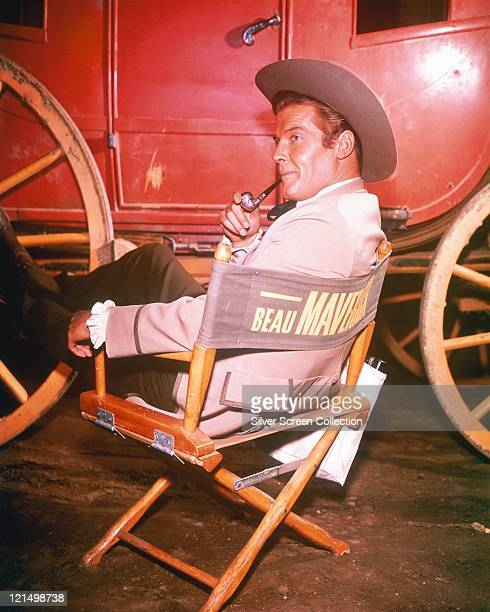 Roger Moore British actor in costume smoking a pipe as he sits in a director's chair with the legend 'Beau Maverick' across the back with a...