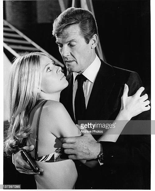 Roger Moore holds a gun as he embraces Britt Ekland who is wearing a bikini top in a scene from the film 'The Man With The Golden Gun' 1974