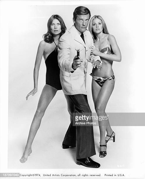 Roger Moore pointing a gun as Britt Ekland and Maud Adams stand on each side of him in their bathing suits in a scene from the film 'The Man With The...