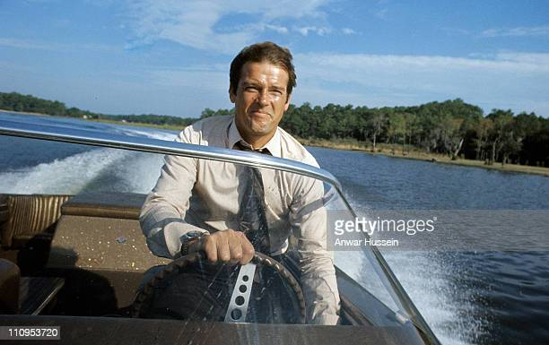 Roger Moore poses driving a speedboat during the filming of James Bond film 'Live And Let Die' on March 1 1973 in Kingston Jamaica