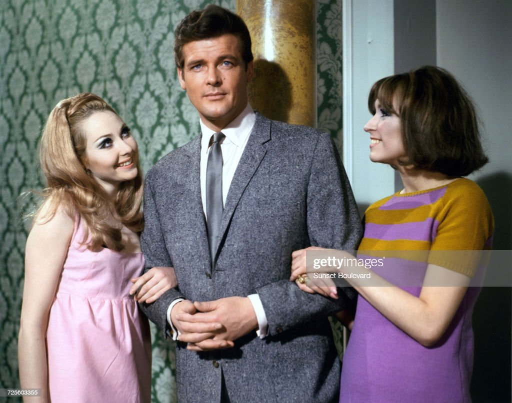 Roger Moore (1927 - 2017) poses with two actresses in a promotional portrait for the TV series, 'The Saint', circa 1967.